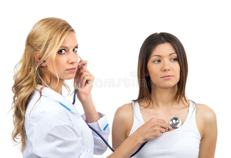 Arts of verpleegster die geduldige stekel met stethoscoop auscultating phys stock afbeeldingen
