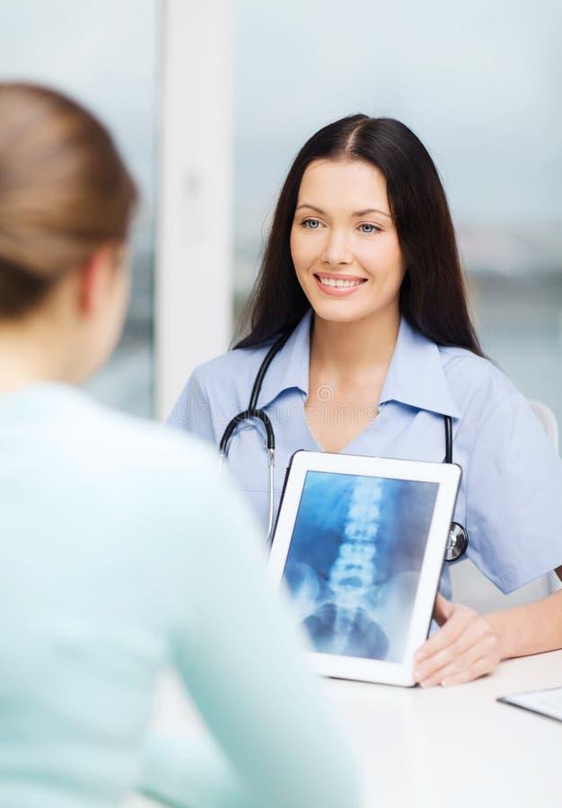 Arts of verpleegster die röntgenstraal met tabletpc tonen stock foto