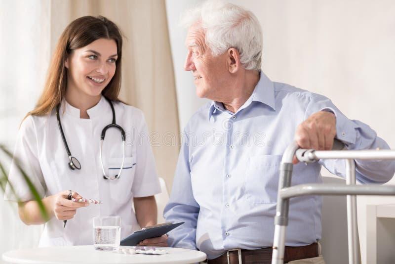 Artsen bezoekende patiënt thuis stock afbeelding