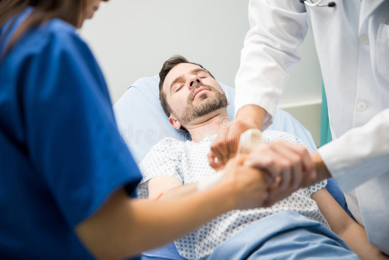 Artsen die aan een unconsious patiënt werken stock foto's