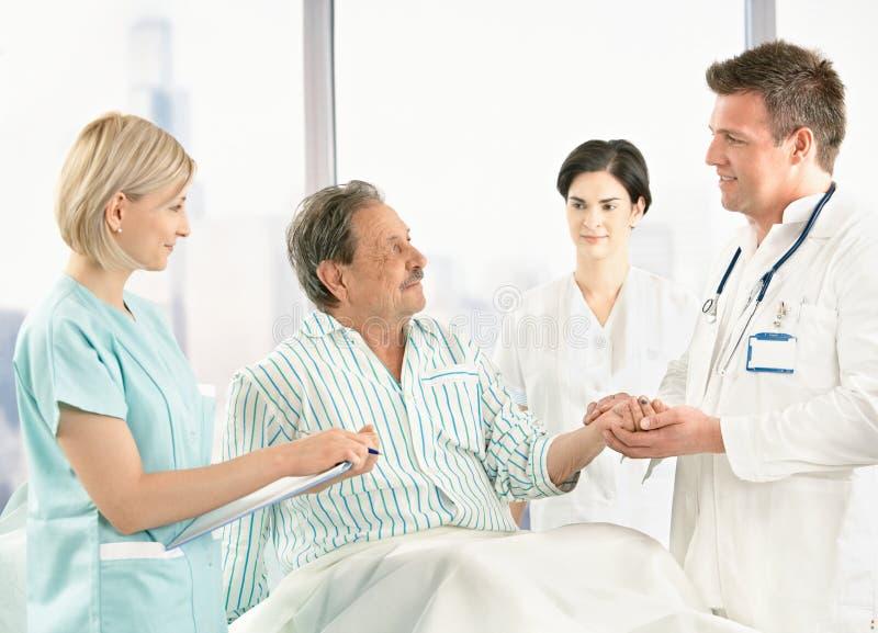 Artsen die aan oude patiënt in het ziekenhuis spreken stock fotografie