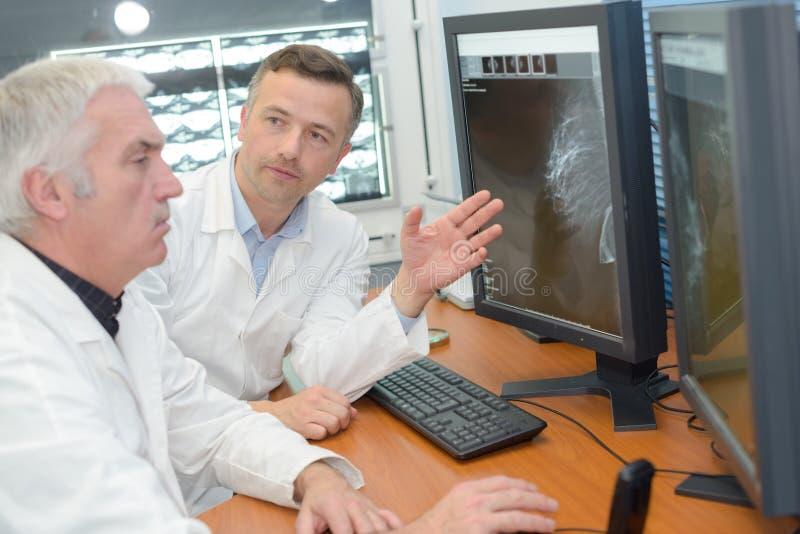 Artsen die aan x-ray aftasten op monitor kliniek bekijken royalty-vrije stock foto