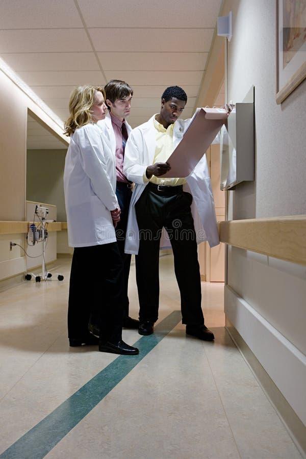 Artsen die geduldige nota's bekijken stock foto's