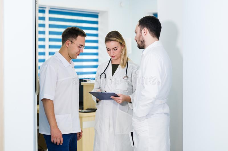 Artsen die in het ziekenhuis werken en over medische rapporten bespreken Medisch personeel die en bij kliniek analyseren werken royalty-vrije stock afbeeldingen