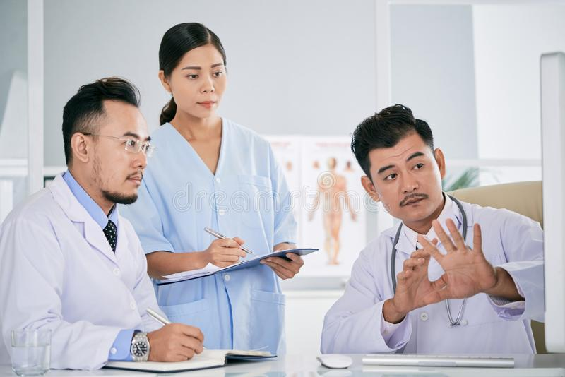 Artsen die moeilijke koffie bespreken stock foto's