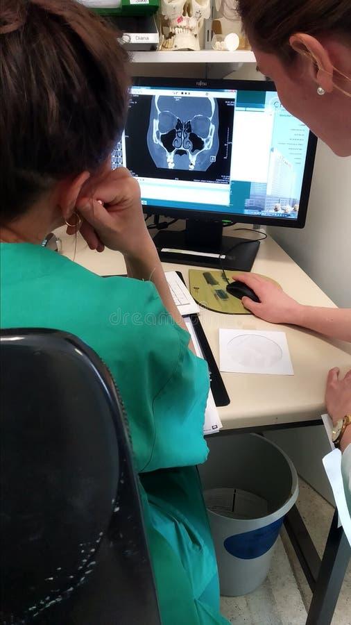 Artsen die MRI op het scherm controleren stock foto