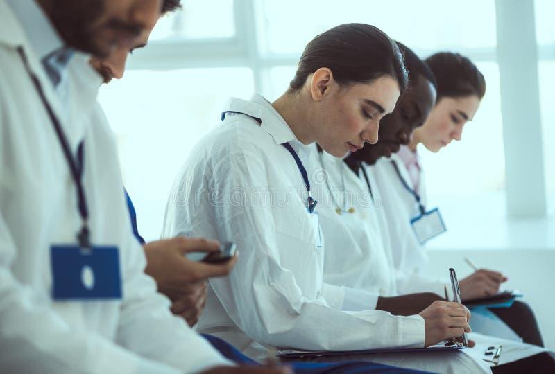 Artsen die nota's nemen tijdens conferentie in de kliniek stock fotografie