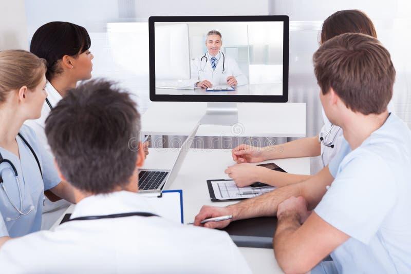 Artsen die op online presentatie letten stock fotografie