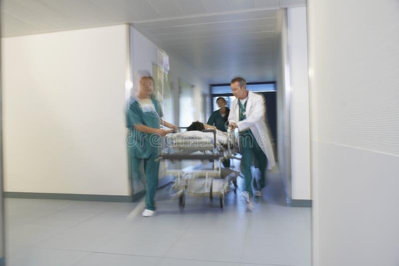 Artsen die Patiënt op Gurney bewegen door het Ziekenhuisgang stock foto's