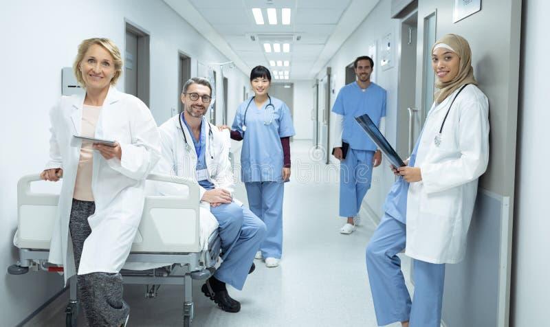 Artsen en chirurgen die camera in de gang bij het ziekenhuis bekijken royalty-vrije stock fotografie