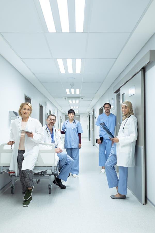 Artsen en chirurgen die camera in de gang bij het ziekenhuis bekijken stock afbeelding