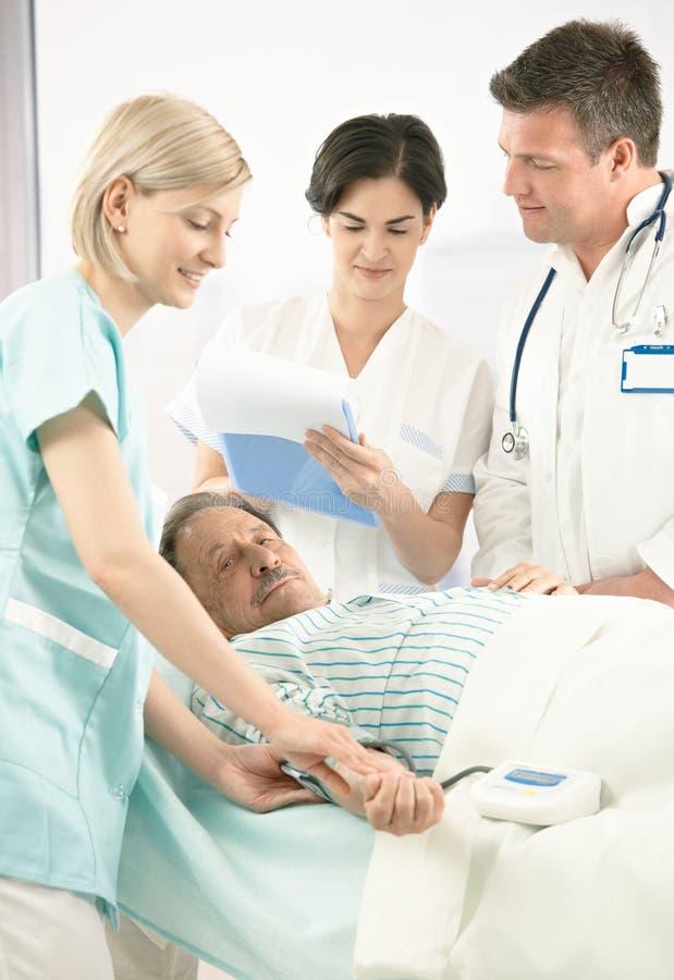 Artsen en verpleegster die patiënt onderzoeken royalty-vrije stock foto's
