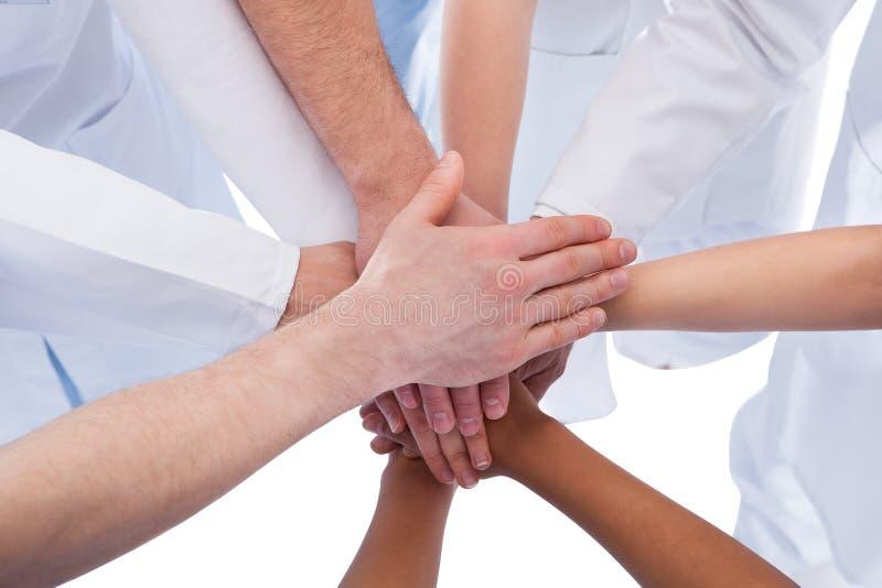 Artsen en verpleegsters die handen stapelen