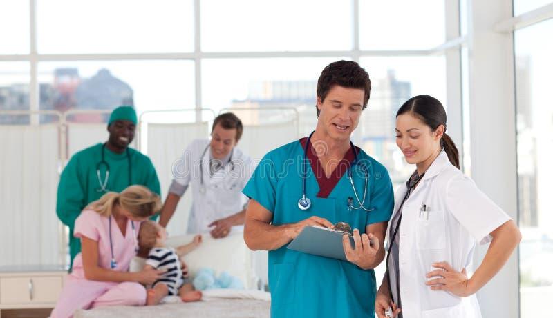 Artsen in het ziekenhuis dat voor een patiënt zorgt stock afbeelding
