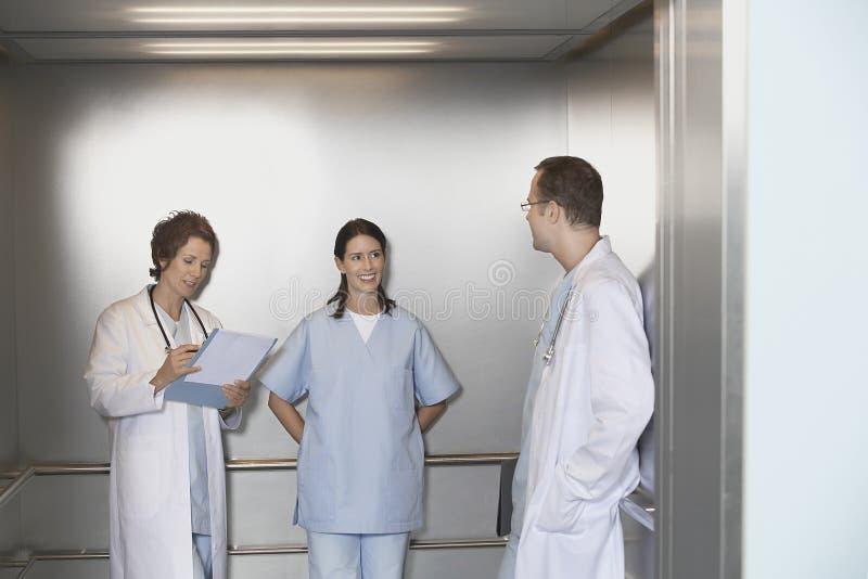 Artsen in Lift het Spreken stock afbeeldingen