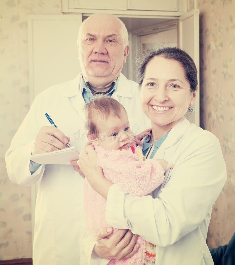 Artsen met baby in binnenland stock foto's