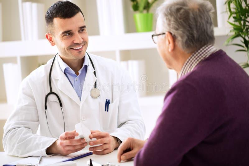 Artsen raadplegende patiënt met geneeskundedrugs stock foto