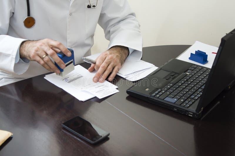 Artsen` s hand op het voorschrift wordt gestempeld dat De arts schrijft een voorschrift bij zijn bureau stock fotografie