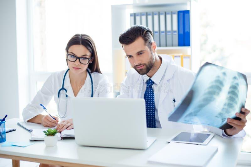 Artsenarbeiders die de röntgenstraal van de patiënt en het controleren analyseren royalty-vrije stock afbeeldingen