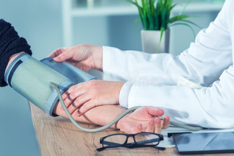 Artsencardioloog die bloeddruk van vrouwelijke patiënt meten stock fotografie