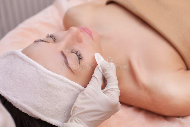 Artsencosmetologist reinigt met een tonicum de gezichtshuid van een mooie, jonge vrouw in een schoonheidssalon stock fotografie