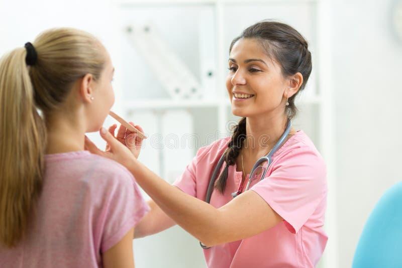 Artsendokter die tiener geduldig meisje in het ziekenhuisbureau onderzoeken, Gezondheidszorgconcept royalty-vrije stock foto's
