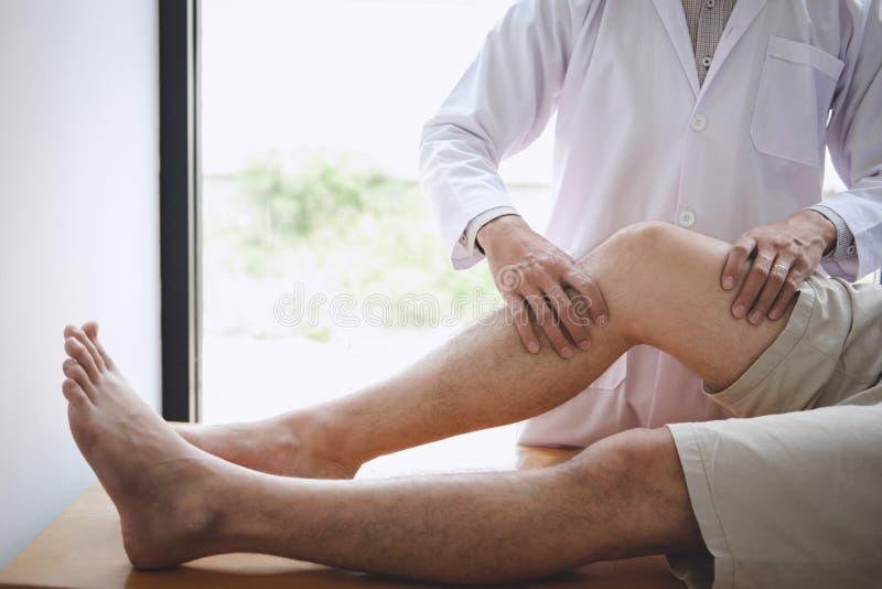 Artsenfysiotherapeut die een mannelijke pati?nt bijstaan terwijl het geven uitoefenend behandeling die het been van pati?nt in ee stock foto's