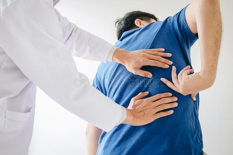 Artsenfysiotherapeut die lagere rugpijnpati?nt behandelen na terwijl het geven uitoefenend behandeling bij zich het uitrekken in  royalty-vrije stock afbeelding