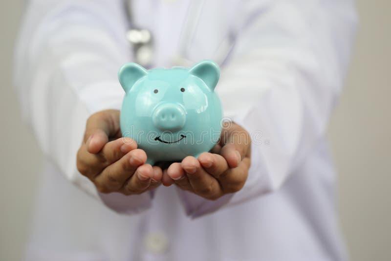 Artsenhand die blauw spaarvarken op witte achtergrond, Ziektekostenverzekeringconcept houden royalty-vrije stock foto's
