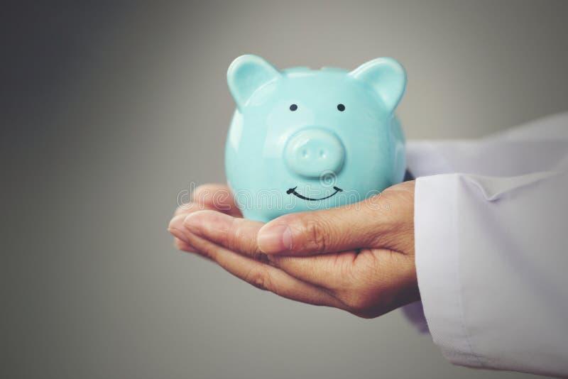 Artsenhand die blauw spaarvarken op witte achtergrond, Ziektekostenverzekeringconcept houden royalty-vrije stock fotografie