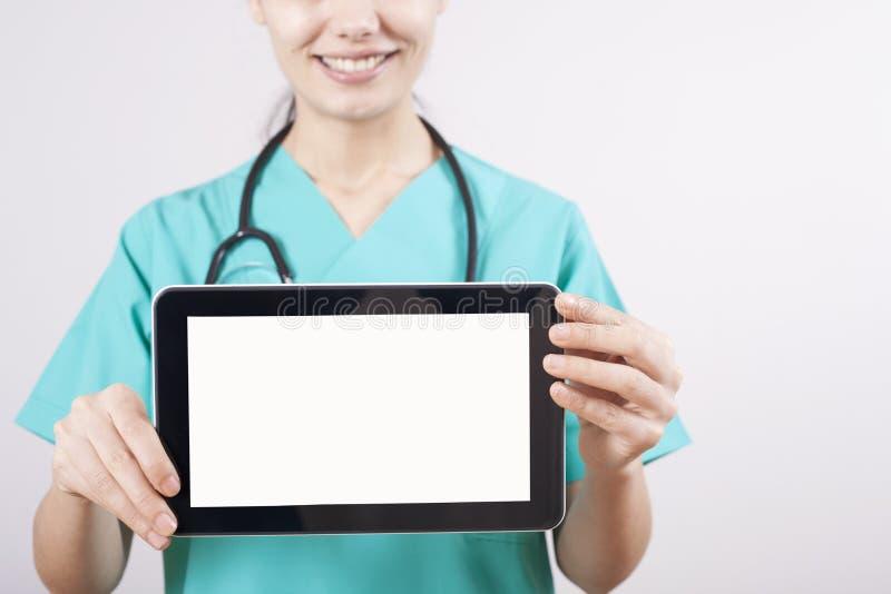 Artsenhand die digitale tablet op grijze achtergrond houden stock fotografie