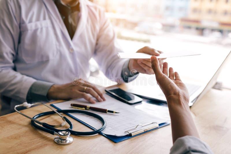 Artsenhand die voorschriftdocument geven aan patiënt stock fotografie