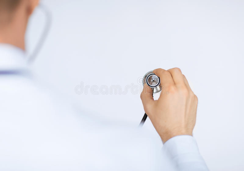 Artsenhand met stethoscoop die somebody luisteren stock fotografie