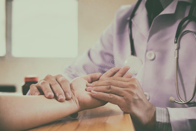 Artsenhanden die impuls op vrouwelijke pols voelen stock foto