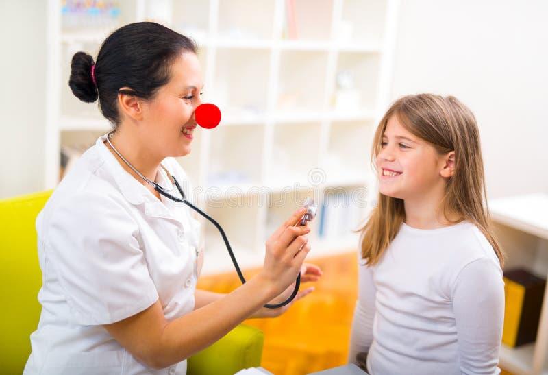Artsenpediater met clownneus en gelukkige kindpatiënt stock fotografie