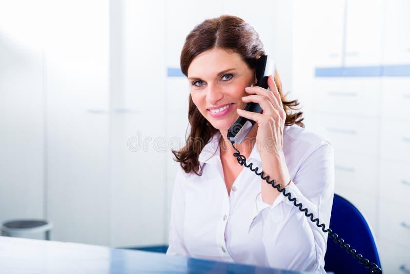 Artsenverpleegster met telefoon vooraan bureau royalty-vrije stock foto's
