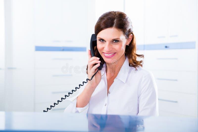 Artsenverpleegster met telefoon vooraan bureau royalty-vrije stock afbeeldingen