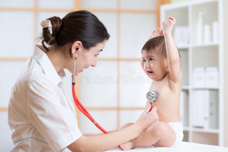 Artsenvrouw die hartslag van kind met stethoscoop onderzoeken royalty-vrije stock foto's