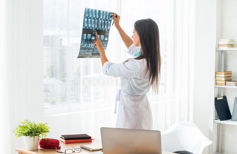 Artsenvrouw die met witte labcoat röntgenstraal bekijken stock afbeeldingen