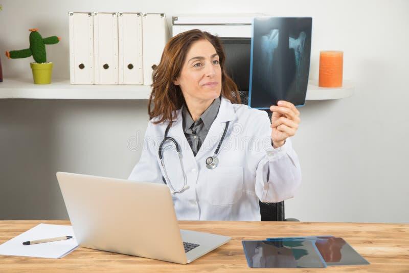 Artsenvrouw die radiografie in bureau bekijken royalty-vrije stock foto