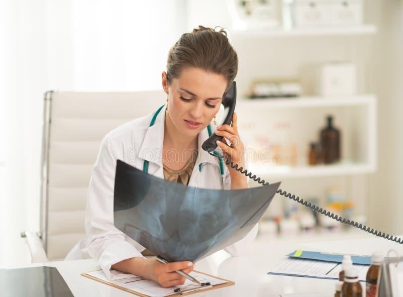 Artsenvrouw met fluorography sprekende telefoon stock foto