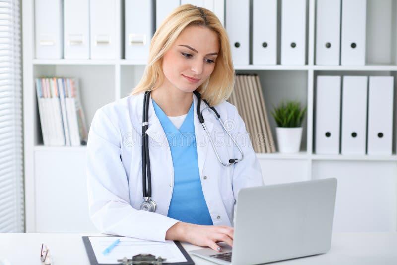 Artsenvrouw op het werk Portret van vrolijke glimlachende blondearts die tabletcomputer met behulp van terwijl het zitten bij het stock fotografie