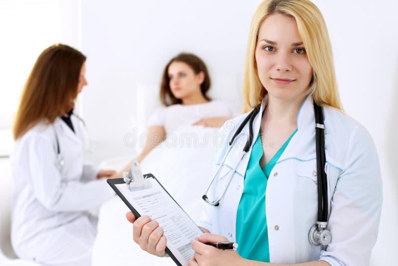 Artsenvrouw of verpleegster in een het ziekenhuisbureau met haar collega en patiënt op de achtergrond Gezondheidszorg en Geneesku stock fotografie