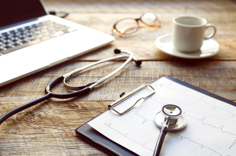 Artsenwerkplaats met een stethoscoop bij houten lijst stock afbeeldingen