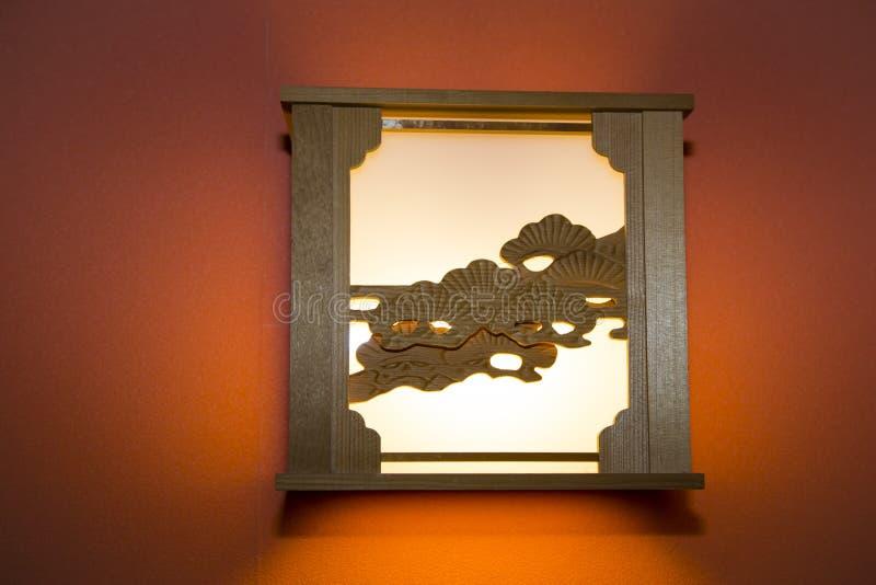 Artsy Holz-geschnitzte Lampe auf orange Wand stockbilder