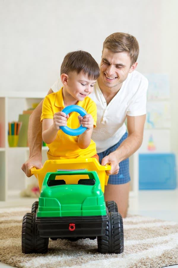 Żartuje chłopiec i tata bawić się z zabawkarskim bagażnikiem obraz royalty free