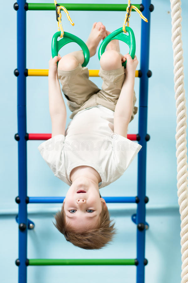 Żartuje chłopiec na gimnastycznych pierścionkach w gym klasie obraz stock