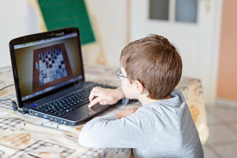 Żartuje chłopiec z szkłami bawić się online szachową grę planszowa na komputerze fotografia stock