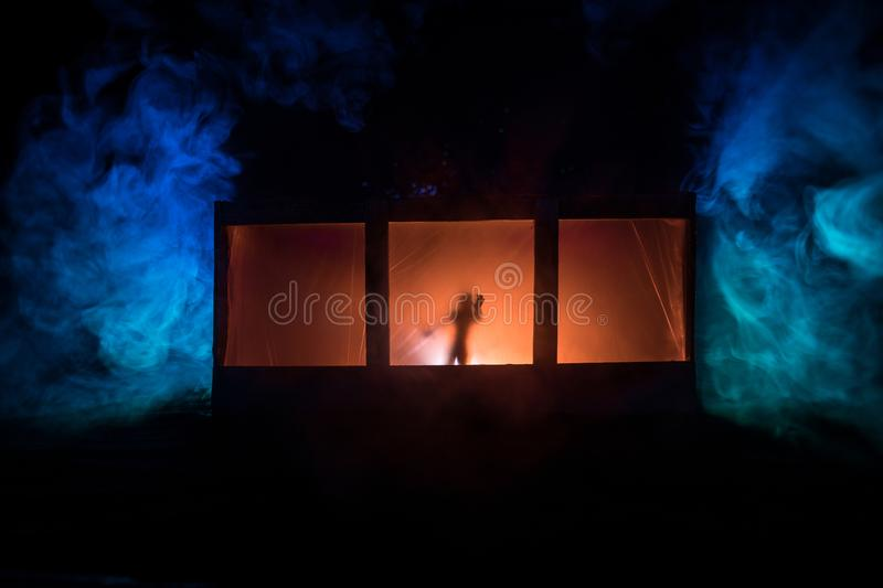 Old house with a Ghost in the forest at night. Horror silhouette at the window. Old building in forest. Surreal lights. Horror royalty free stock photography