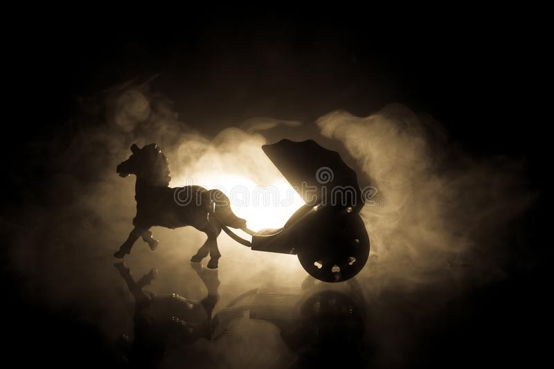 Artwork decoration. Silhouette of old coach with horse on dark toned foggy background. Selective focus royalty free stock photography
